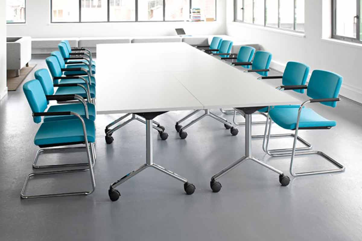 Foldable meeting room table with colourful chairs